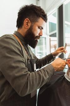Erwachsener friseur, der kundenhaar am friseursalon trimmt
