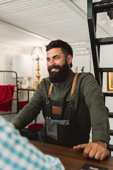 Erwachsener friseur, der mit kunden am friseursalon spricht