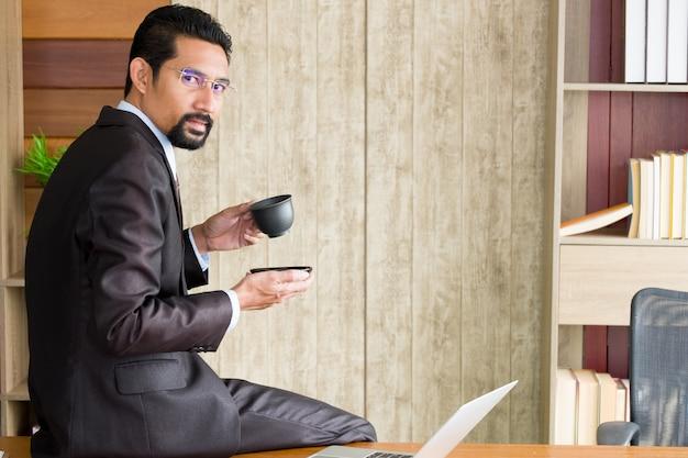 Erwachsener geschäftsmann, der auf dem schreibtisch sitzt und kaffeetasse hält.