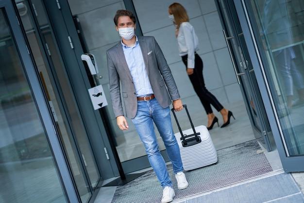 Erwachsener geschäftsmann, der das hotel aufgrund von covid-19-beschränkungen mit maske verlässt