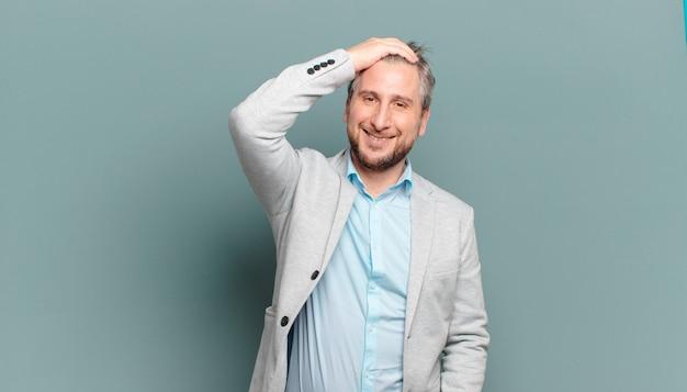Erwachsener geschäftsmann, der fröhlich und beiläufig lächelt und hand an kopf mit einem positiven, glücklichen und selbstbewussten blick nimmt
