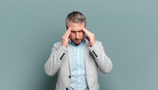 Erwachsener geschäftsmann, der gestresst und frustriert aussieht, unter druck mit kopfschmerzen arbeitet und probleme hat