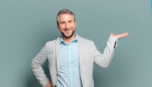 Erwachsener geschäftsmann, der lächelt, sich sicher, erfolgreich und glücklich fühlt und konzept oder idee auf kopienraum auf der seite zeigt