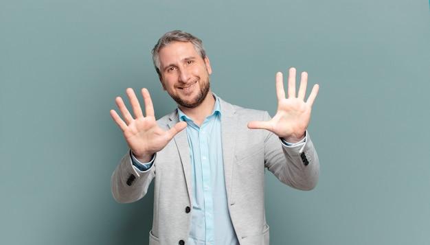 Erwachsener geschäftsmann, der lächelt und freundlich aussieht, nummer zehn oder zehntel mit der hand vorwärts zeigend, herunterzählend