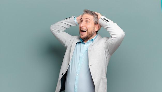 Erwachsener geschäftsmann mit offenem mund, der wegen eines schrecklichen fehlers entsetzt und schockiert aussieht und die hände zum kopf hebt