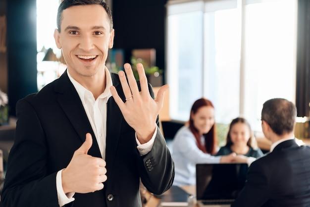 Erwachsener glücklicher mann zeigt ring auf seinem finger und zeigt sich daumen
