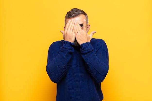 Erwachsener gutaussehender mann, der das gesicht mit den händen bedeckt, mit überraschtem ausdruck zwischen den fingern späht und zur seite schaut