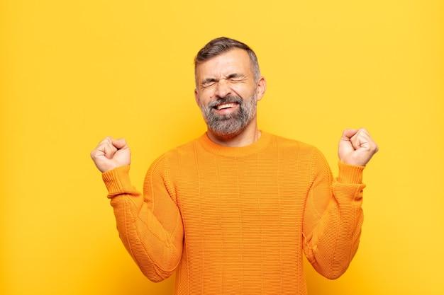 Erwachsener, gutaussehender mann, der extrem glücklich und überrascht aussieht, erfolg feiert, schreit und springt