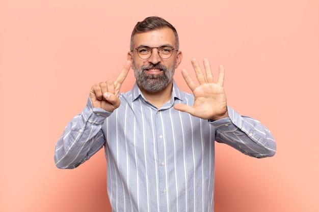 Erwachsener gutaussehender mann, der lächelt und freundlich aussieht, nummer sechs oder sechste mit der hand vorwärts zeigend, herunterzählend