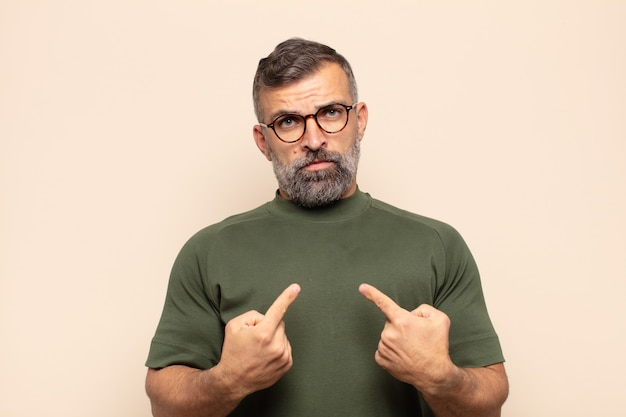 Erwachsener gutaussehender mann, der mit einem verwirrten und fragenden blick auf sich selbst zeigt, schockiert und überrascht, ausgewählt zu werden