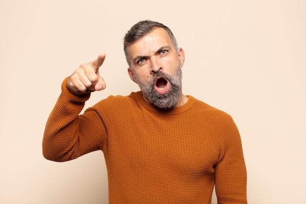 Erwachsener gutaussehender mann, der mit einem wütenden aggressiven ausdruck auf kamera zeigt, der wie ein wütender, verrückter chef aussieht