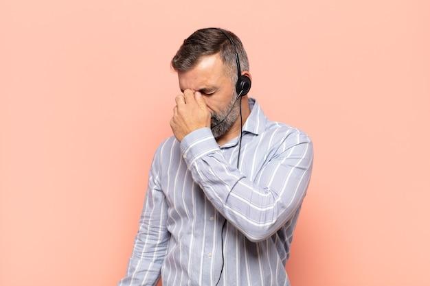 Erwachsener gutaussehender mann, der sich gestresst, unglücklich und frustriert fühlt, die stirn berührt und unter migräne mit starken kopfschmerzen leidet