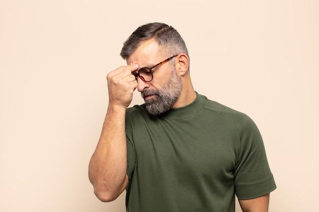 Erwachsener, gutaussehender mann, der sich gestresst, unglücklich und frustriert fühlt, die stirn berührt und unter migräne mit starken kopfschmerzen leidet