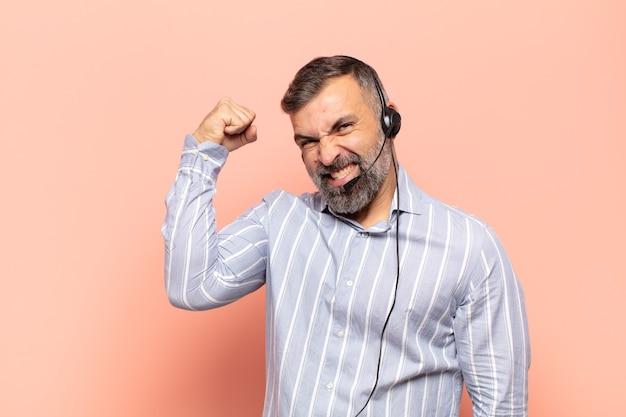 Erwachsener gutaussehender mann, der sich glücklich, zufrieden und kraftvoll fühlt, passform und muskulösen bizeps, stark nach dem fitnessstudio schauend