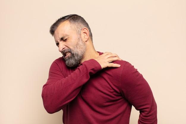 Erwachsener gutaussehender mann, der sich müde, gestresst, ängstlich, frustriert und depressiv fühlt und unter rücken- oder nackenschmerzen leidet
