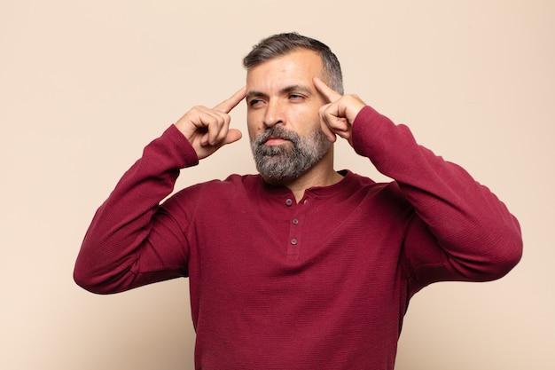 Erwachsener gutaussehender mann, der sich verwirrt oder zweifelnd fühlt, sich auf eine idee konzentriert, hart nachdenkt und versucht, platz auf der seite zu kopieren