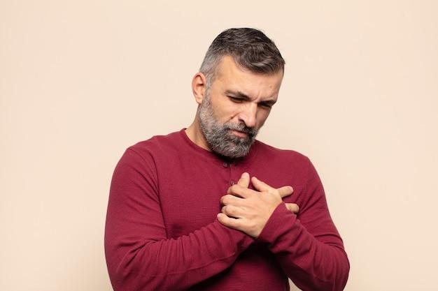 Erwachsener gutaussehender mann, der traurig, verletzt und mit gebrochenem herzen aussieht, beide hände nah am herzen hält, weint und sich depressiv fühlt