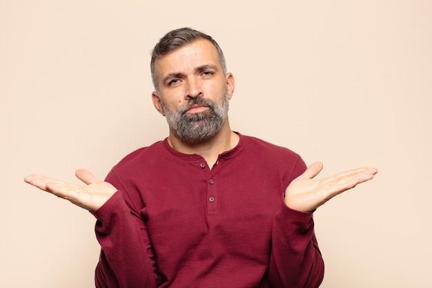 Erwachsener gutaussehender mann, der verwirrt, verwirrt und gestresst aussieht, sich zwischen verschiedenen optionen wundert und sich unsicher fühlt
