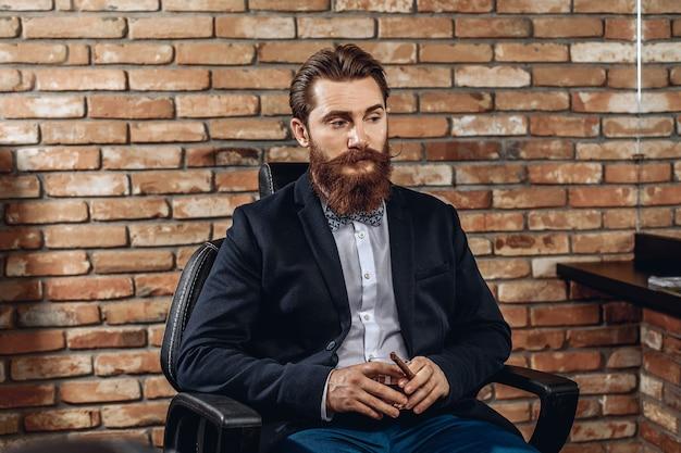 Erwachsener gutaussehender mann in einem anzug, der auf dem sitz sitzt und ein glas whisky und eine zigarre in seinen händen hält. brutales konzept