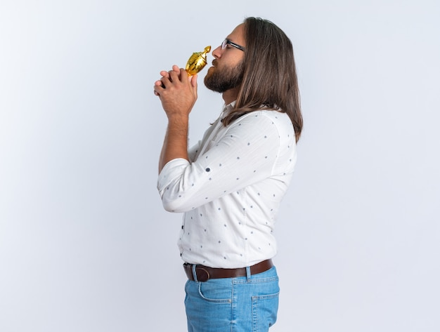 Erwachsener, gutaussehender mann mit brille, der in der profilansicht steht und siegerpokal in der nähe des mundes mit geschlossenen augen hält, isoliert auf weißer wand mit kopierraum