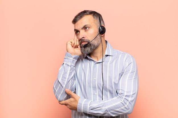 Erwachsener, gutaussehender mann mit konzentriertem blick, der mit einem zweifelnden gesichtsausdruck verwundert und nach oben und zur seite schaut