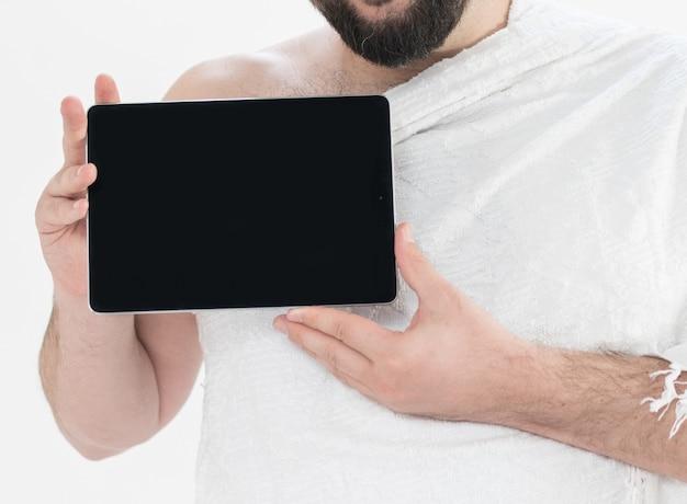 Erwachsener hajj, der tablette hält