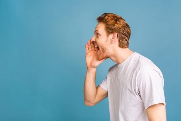 Erwachsener hispanischer mann, der mit der hand auf dem mund laut zur seite schreit und schreit. kommunikationskonzept.