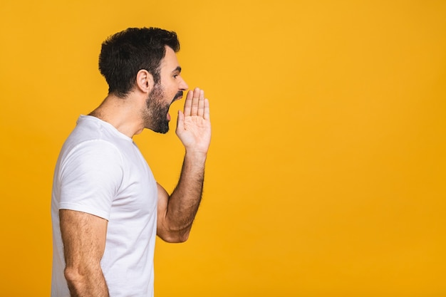 Erwachsener hispanischer mann über isoliertem gelbem hintergrund, der laut zur seite mit der hand auf mund schreit und schreit.
