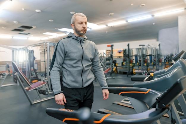 Erwachsener hübscher bärtiger mann, der körperliche übungen tut