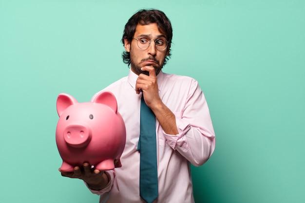 Erwachsener hübscher indischer geschäftsmann mit einem sparschwein