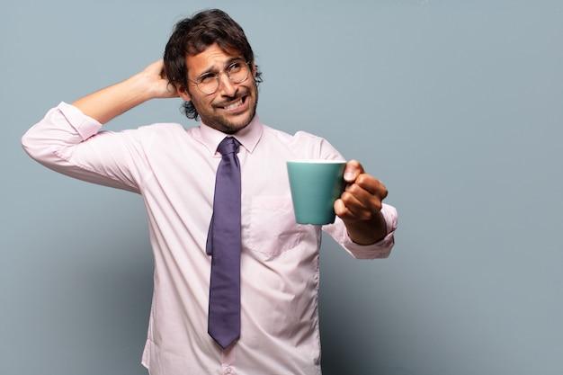Erwachsener hübscher indischer geschäftsmann mit einer kaffeetasse