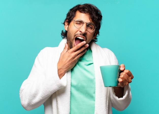 Erwachsener hübscher indischer mann, der bademantel trägt und einen kaffee hat