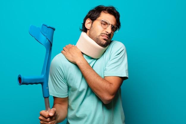 Erwachsener hübscher indischer mann, der einen unfall erlitten hat. krücken- und kragenkonzept