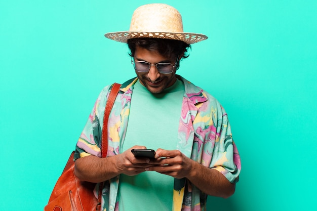 Erwachsener hübscher indischer touristenmann, der heu und eine ledertasche trägt und seine zelle benutzt