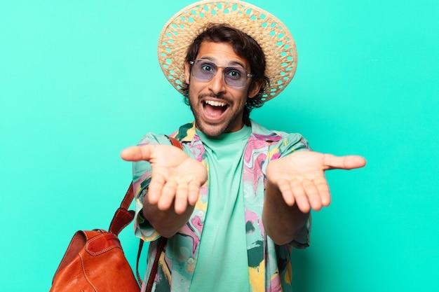 Erwachsener hübscher indischer touristenmann, der heu und eine ledertasche trägt