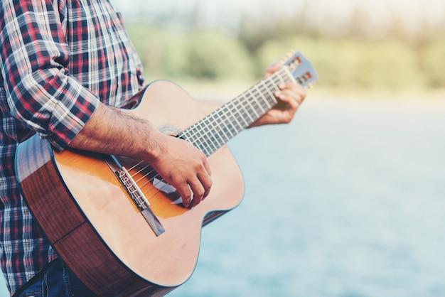 Erwachsener hübscher musiker, der akustische gitarre spielt
