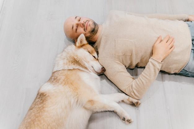 Erwachsener kahler mann mit husky-welpen, der auf boden schläft. besitzer mit haustier zusammen zu hause. schöner hund, der mit jungem mann ruht. kerl mit geliebtem haustier, das sich umarmt.