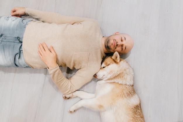 Erwachsener kahler mann mit husky-welpen, der auf boden schläft. besitzer mit haustier zusammen zu hause. schöner hund, der mit jungem mann ruht.