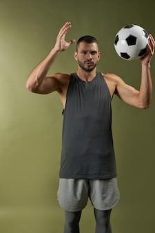 Erwachsener kaukasischer gutaussehender fußballtrainer in aktion mit ball im innenbereich