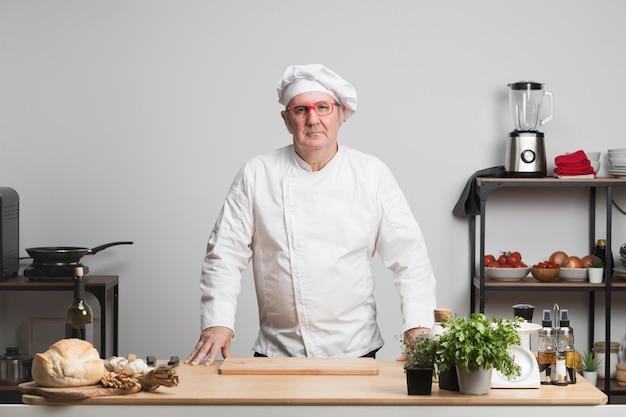 Erwachsener koch der vorderansicht in der küche