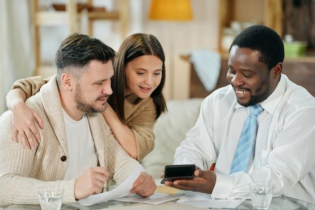 Erwachsener lächelnder schwarzer mann mit rechenmaschine, die junges paar ihren zinssatz zeigt