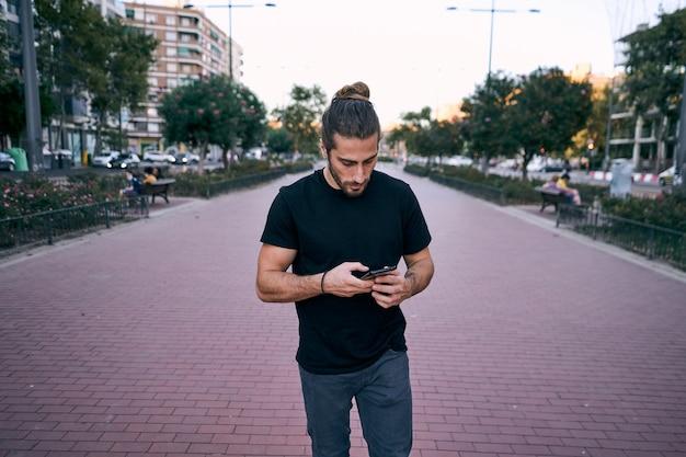Erwachsener langhaariger mann, der auf der straße geht, während er einen geschäftlichen telefonanruf hat