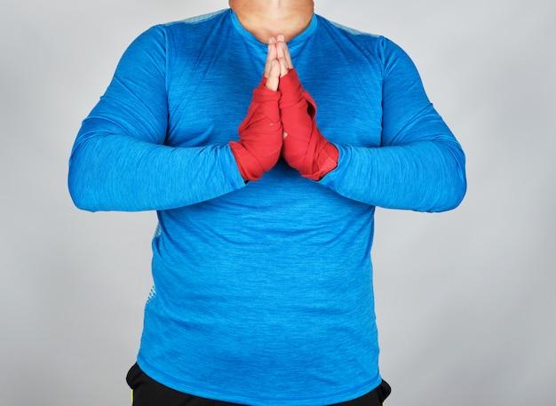 Erwachsener männlicher athlet in der blauen uniform ist in der gebetshaltung