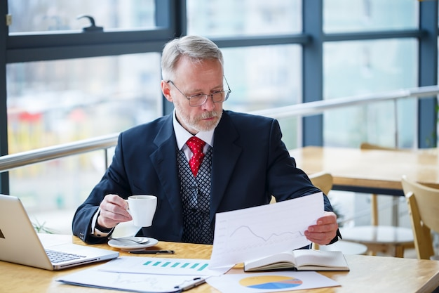 Erwachsener männlicher geschäftsmann, der an einem neuen projekt arbeitet und aktienwachstumsdiagramme betrachtet. sitzt an einem großen fenster am tisch. schaut auf den laptop-bildschirm und trinkt kaffee.
