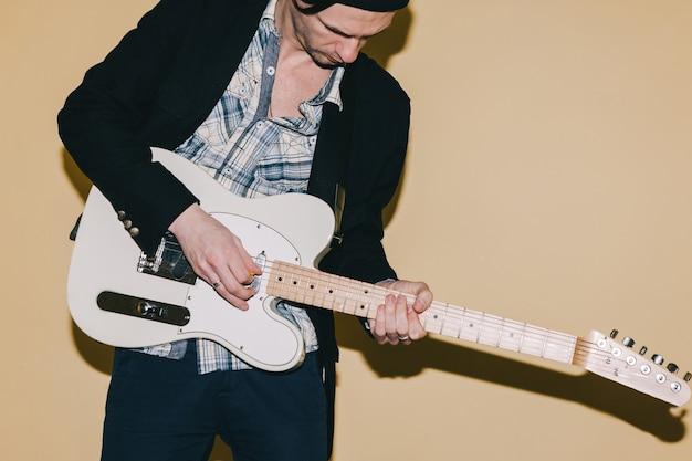 Erwachsener männlicher gitarrist, der eifrig gitarre spielt