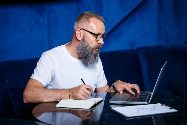 Erwachsener männlicher mentor, direktor, geschäftsmann in brille und anzug, der dokumente studiert, während er am tisch sitzt. konzept des arbeitstages