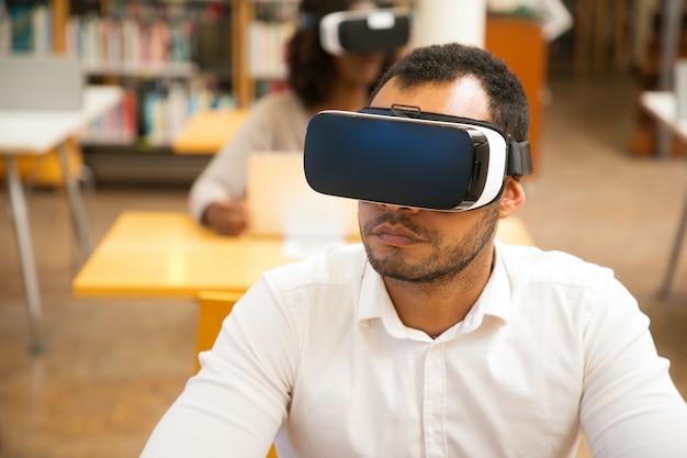 Erwachsener männlicher student, der vr-gläser beim arbeiten in der bibliothek verwendet