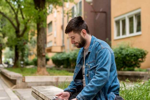 Erwachsener mann, der auf bank sitzt und smartphone verwendet
