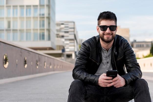 Erwachsener mann, der auf dem boden hält smartphone sitzt