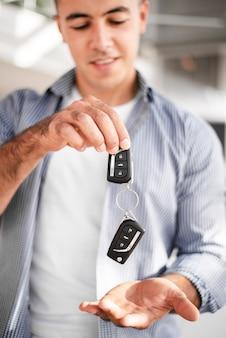 Erwachsener mann, der autoschlüssel hält